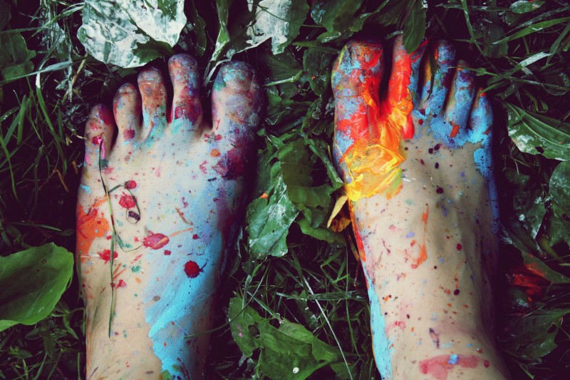 Bare feet spattered with paint standing on leaf-strewn grass